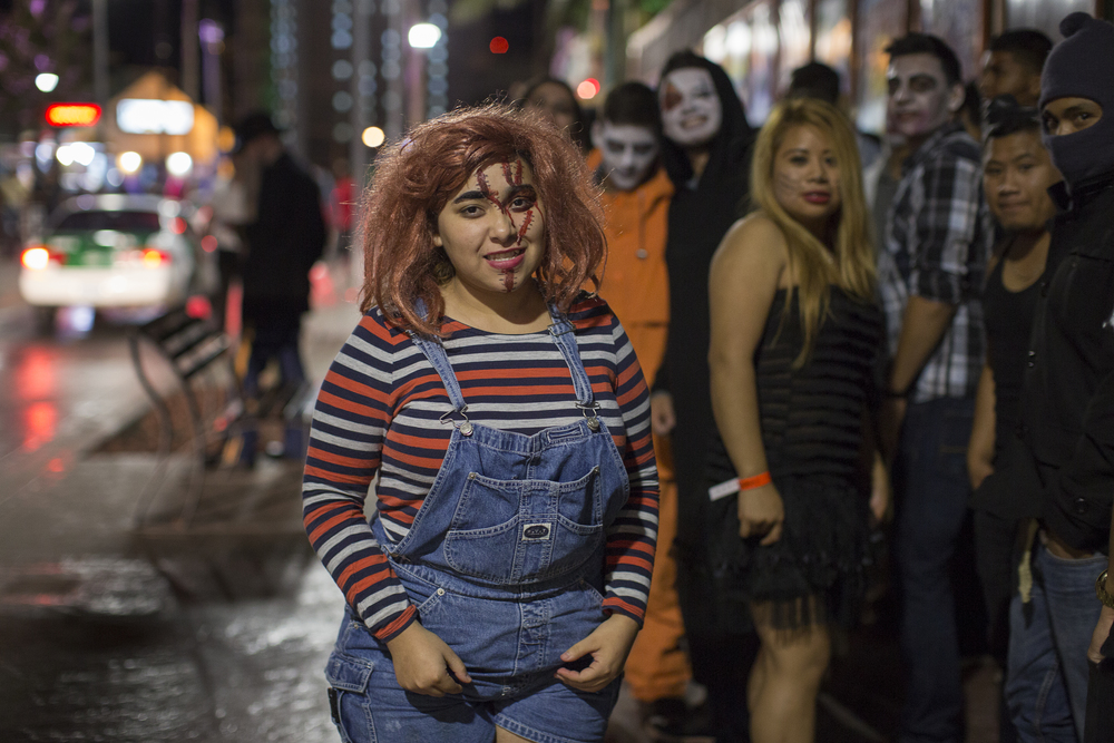 A woman stands in line at Papas and Beer, a popular night club in Rosarito on Oct. 31, 2015 dressed as Chuck, an iconic American horror character. (Griselda San Martin)