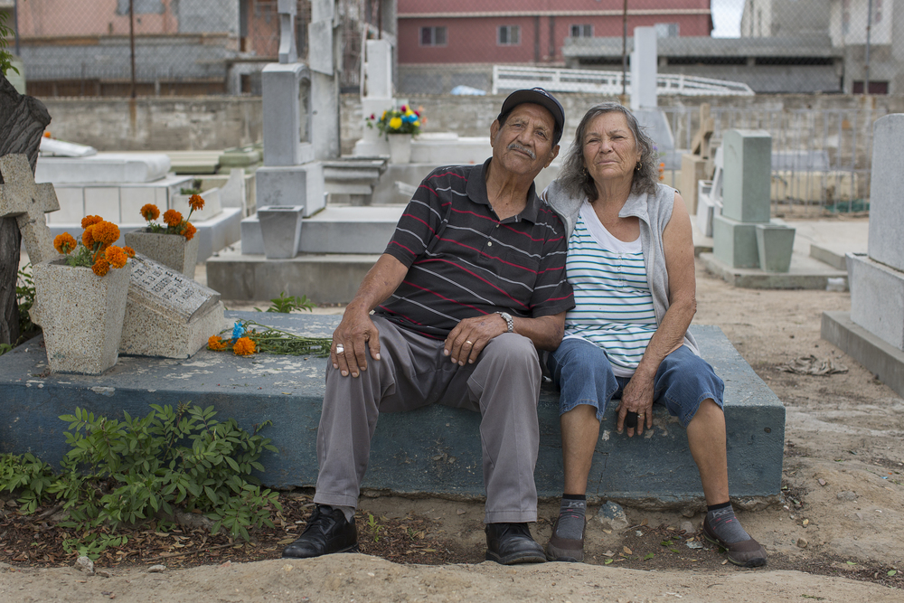 Mardoqueo Mendoza, 83, and Clara Quesada 75, pose for a portrait at Pantéon Numero 1, Tijuana's largest cemetery, on Nov 2, 2015 at the gravesite of Mendoza's brother who passed away at 19 in a car accident in Rosarito. (Griselda San Martin)