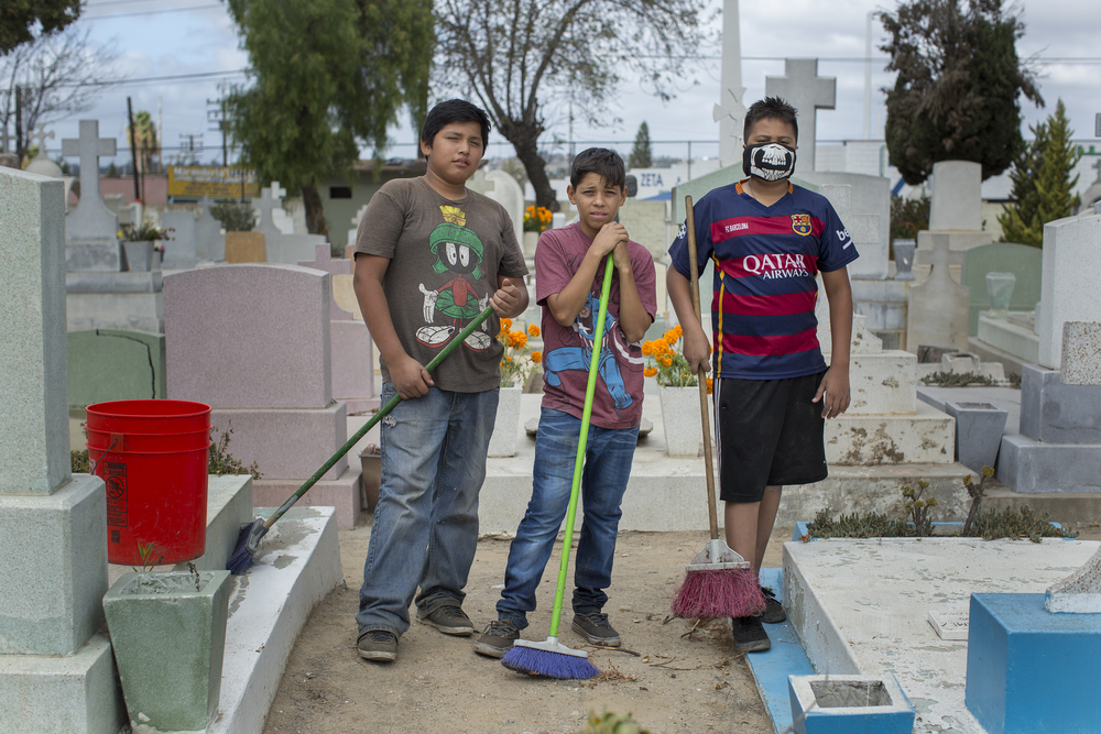 Kids from the neighborhood close to the Pantéon Numero Uno, Tijuana's largest cemetery, from left, Armando Daniel, Brian Salcedo and Eddie Ramirez pose for a portrait on Nov. 2, 2015 or Día De Los Muertos. Kids from all over Tijuana come to the cemetery on Día De Los Muertos to offer cleaning services to families who come to visit. (Griselda San Martin)