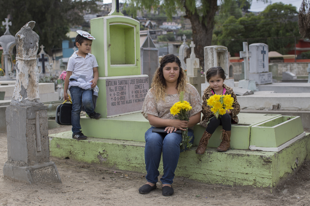 Priscilla Preciado, 24, sits next to her daughter Nicole Vargas, 4, and her son Anibal Vargas, 5, on Nov. 2, 2015 at Pantéon Numero 1, Tijuana's largest cemetery to honor and visit their grandfather. (Griselda San Martin)