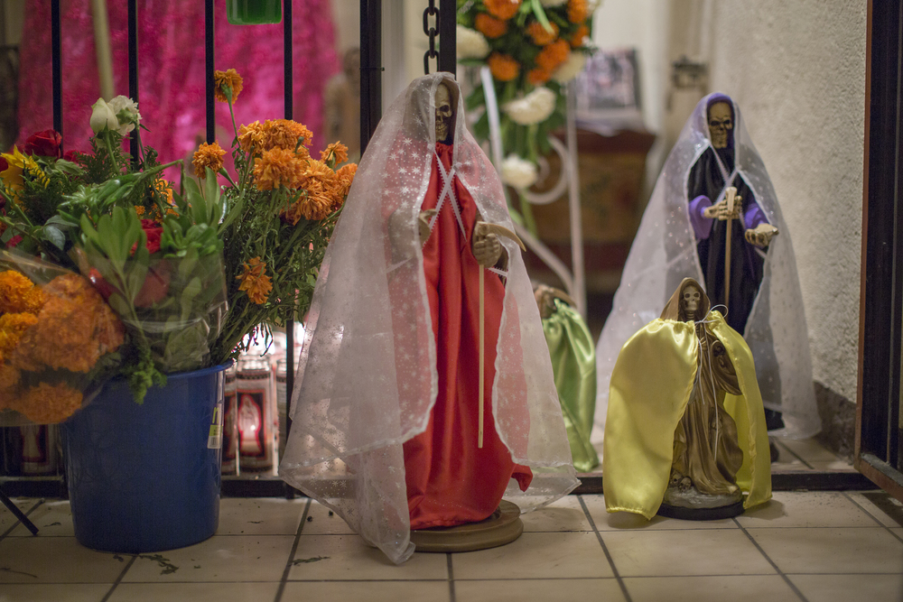 Smaller Santa Muerte figurines line the bottom of a larger altar on Nov. 1, 2015 at the Botanica La Chula, a store and gathering place for Santa Muerte Followers in a neighborhood on the outskirts of Tijuana. (Griselda San Martin)