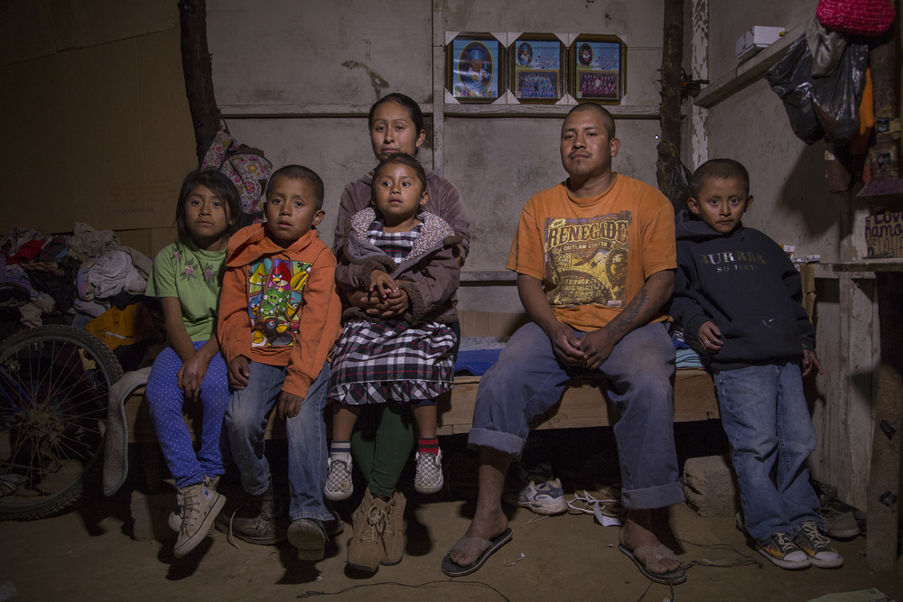 Federico Pastrana and his wife Isabel Policao sit with their four children inside their house made of cardboard and plastic. Pastrana and Policao both work in the fields and make $9 a day. The lot where they constructed their house cost them 40,000 pesos, which is around $2,300. They are paying for it little by little. (Griselda San Martin)