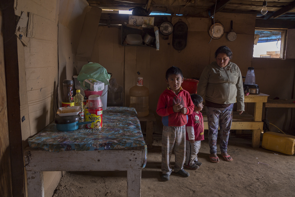 Cecilia Sanchez, 25, poses with her children Eric, 5, and Adair, 2, in the kitchen area of their little cardboard house. (Griselda San Martin)