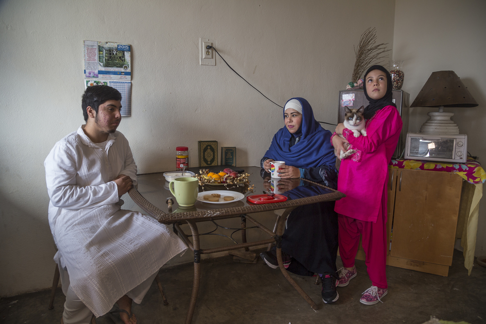 Fatima Castañeda sits with her son Carlos and daughter Nahomi in the living room of their apartment in Rosarito. (Photo by Griselda San Martin)