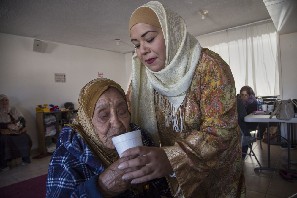 Fatima Castañeda serves Alejandra a cup of water at a gathering in the mosque of Omar, in Playas de Tijuana.    (Photo by Griselda San Martin)