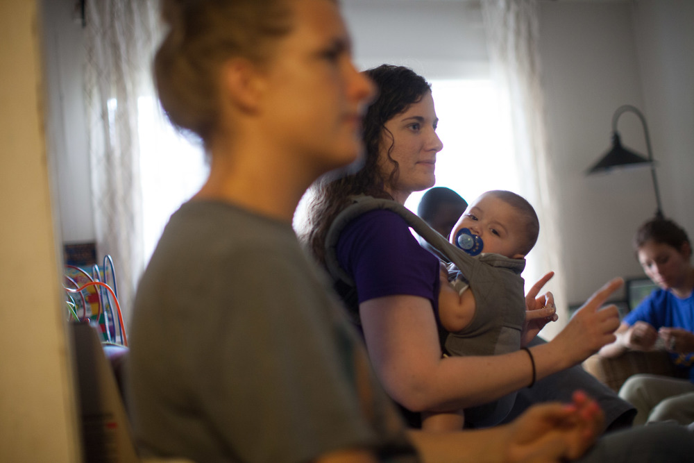 Emory University student Debra Kozowski, left, listens as Katie Valencia, center, holding her son Oscar, briefs other volunteers on visits they will be making to Stewart Detention Center , Saturday, Sept. 12, 2015, in Lumpkin, Ga. (Photo by Branden Camp)