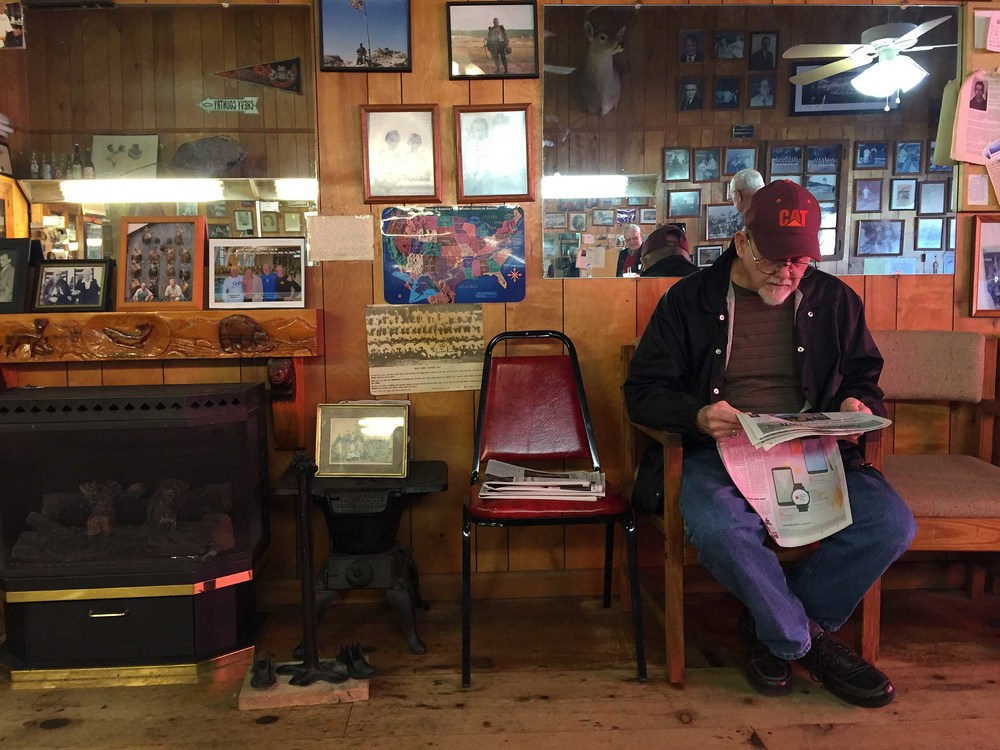A man reads a newspaper while he waits to get his hair cut at the City Barber Shop in downtown Ellijay, Ga. BRANDEN CAMP FOR THE BOSTON GLOBE
