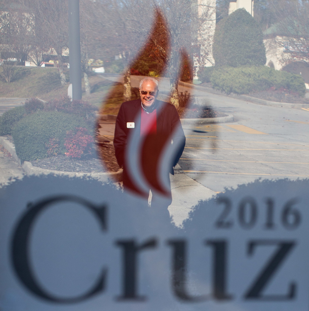 Joe McCutchen is reflected in the window of a local business that is promoting Republican presidential candidate Tex Cruz, Saturday, Dec. 5, 2015, in Ellijay, Ga.