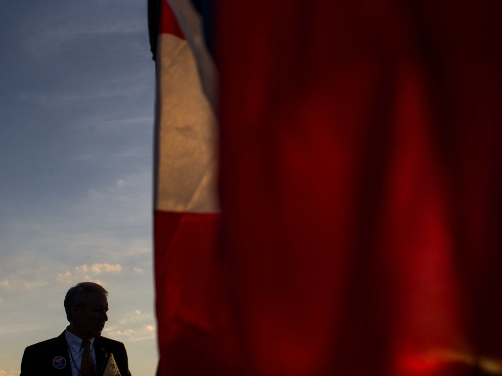 A man is silhouetted against the sky, Monday, Nov. 30, 2015 at the Macon Centreplex in Macon, Ga. where Republican presidential candidate Donald Trump is set to hold a campaign rally .  (AP Photo/Branden Camp)