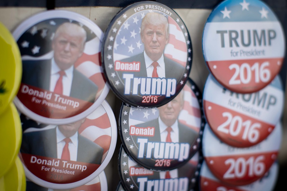 Election pins of Republican presidential candidate Donald Trump sit on display before a campaign rally, Monday, Nov. 30, 2015 at the Macon Centreplex in Macon, Ga.  (AP Photo/Branden Camp)