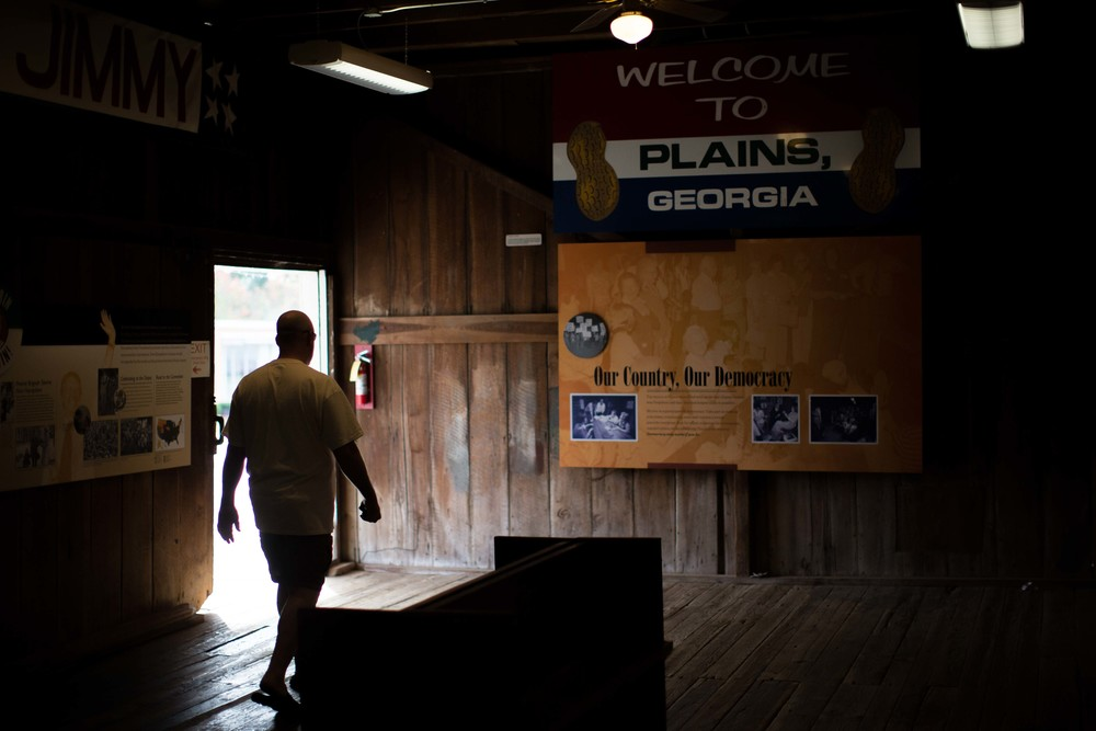 "A man walks through former President Jimmy Carters' campaign headquarters in downtown Plains, Ga.,   Sunday, Dec. 13, 2015.  A recent MRI showing no cancer on Jimmy Carter's brain is ""very positive"" news for the former president but will not end his medical treatment, doctors said. Carter, 91, announced Dec. 6 that doctors found no evidence of the four lesions discovered on his brain this summer and no signs of new cancer growth. (AP Photo/Branden Camp)"