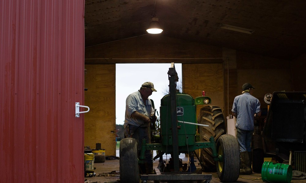 Farmer Phil Sanders, left, and Chance Fowler, 20, right, work on a John Deere tractor at Buffalo Creek Straw and Seed Farm, Wednesday, Feb. 3, 2016, in Stephens, Ga.  With over 42,000 farmers working in the Georgia agriculture industry, farming contributes over $73 Billion to Georgia's economy each year.  Forecasters say profits are expected be down as well as exports in 2016 nationwide due to a fragile world economy.  Photo by Branden Camp