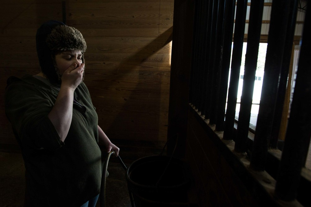 Rebecca Thompson yawns while she works inside a horse stable on a cold day, Wednesday, Feb. 10, 2016, in Woodstock, Ga. (AP Photo/Branden Camp)