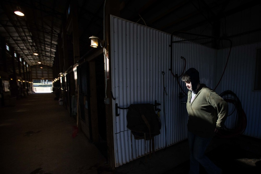 Rebecca Thompson works inside a horse stable on a cold day, Wednesday, Feb. 10, 2016, in Woodstock, Ga. (AP Photo/Branden Camp)