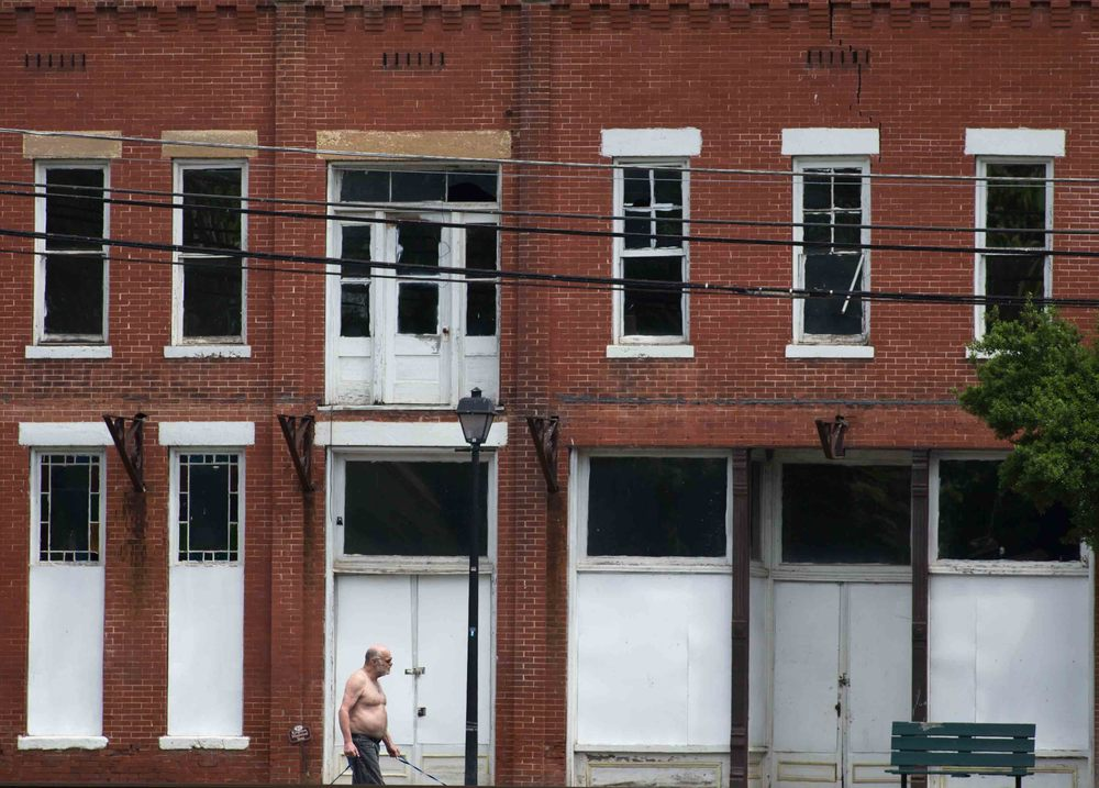 A Kingston resident walks his dogs past DeSoto Hotel, one of many vacant buildings in downtown Kingston. Photo by Branden Camp