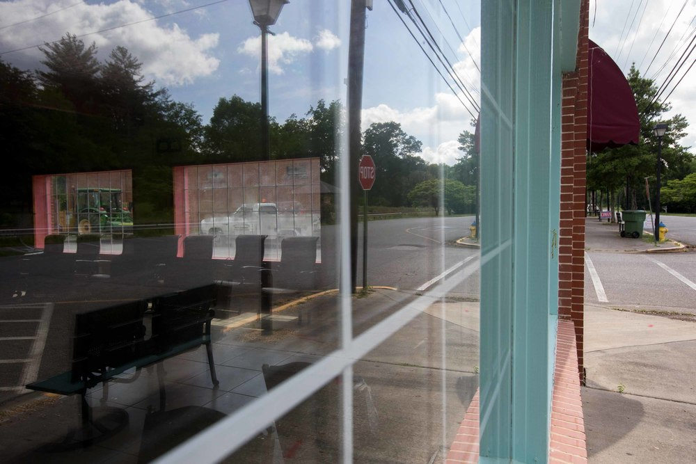 A tractor and a utility truck are seen through the windows what used to be a restaurant in downtown Kingston, Ga.