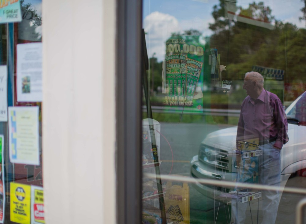 86-year-old G.B. Hood, who has lived in Kingston his whole life, is reflected in the doors of a local convenience store in downtown Kingston, Ga.