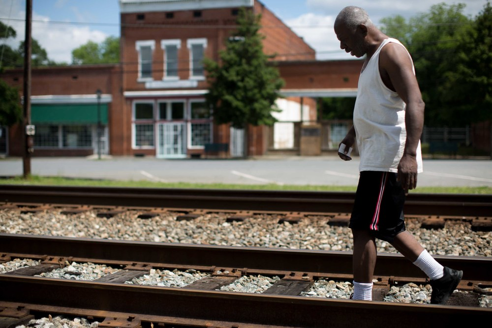 Kingston, Georgia resident Ronald Lee crosses over the railroad tracks in downtown Kingston, Friday, May 13, 2016. Kingston, like many small American towns, are becoming vacant. Lee says that due to extremely low water pressure, businesses don't have sufficient water pressure to operate their businesses.