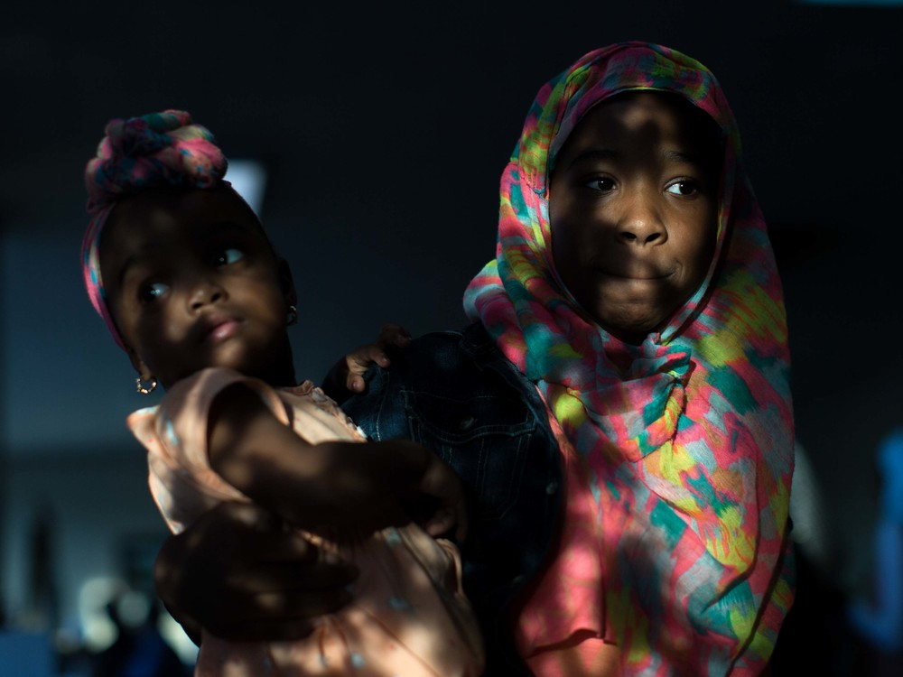 June 9, 2016 - Atlanta, Ga, U.S - Light shines on the face of Khadija Pegues, 13, right, as she holds her 2-year-old sister, Khatima Pegues, following an interfaith service at the Atlanta Masjid of Al Islam mosque in Atlanta. People gathered to honor the late Muhammad Ali, who died on June, 3, 2016, in Phoenix, Arizona.