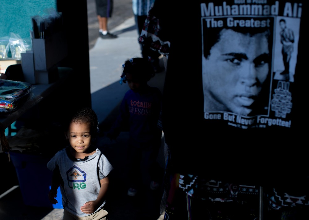 June 9, 2016 - Atlanta, Ga, U.S - Children run past a Muhammad Ali shirt hanging on display at the Atlanta Masjid of Al Islam mosque in Atlanta. People gathered for an interfaith service to honor the late Muhammad Ali, who died on June, 3, 2016, in Phoenix, Arizona.