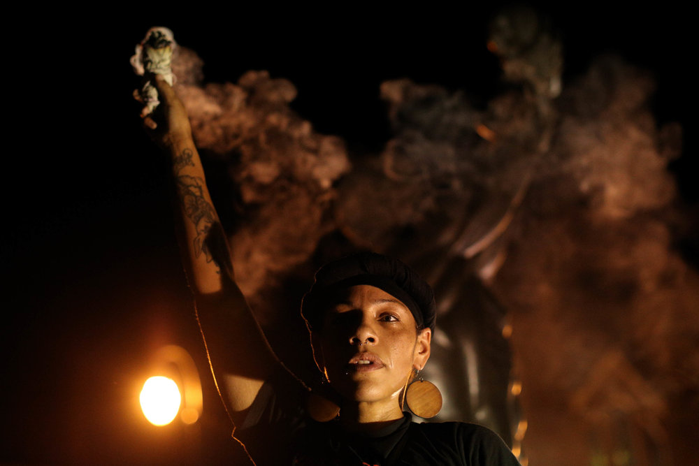 A demonstrator burns sage at the Martin Luther King Jr. Historical Site during a protest in Atlanta on Friday, Sept. 23, 2016 in response to the police shooting deaths of Terence Crutcher in Tulsa, Okla. and Keith Lamont Scott in Charlotte, N.C. (AP Photo/Branden Camp)