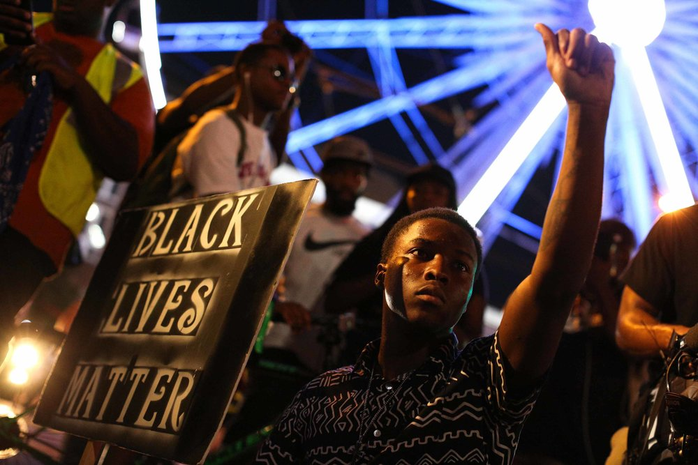 A demonstrator holds a sign during a protest in Atlanta on Friday, Sept. 23, 2016 in response to the police shooting deaths of Terence Crutcher in Tulsa, Okla. and Keith Lamont Scott in Charlotte, N.C. (AP Photo/Branden Camp)