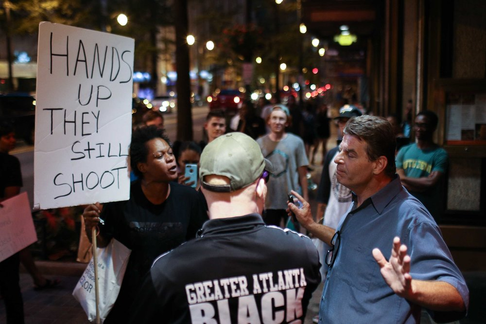 Black Lives Matter protesters argue with a man outside a restaurant during a protest in downtown Atlanta, Saturday, Sept. 24, 2016, in response to the police shooting deaths of Terence Crutcher in Tulsa, Okla. and Keith Lamont Scott in Charlotte, N.C.  (AP Photo/Branden Camp)