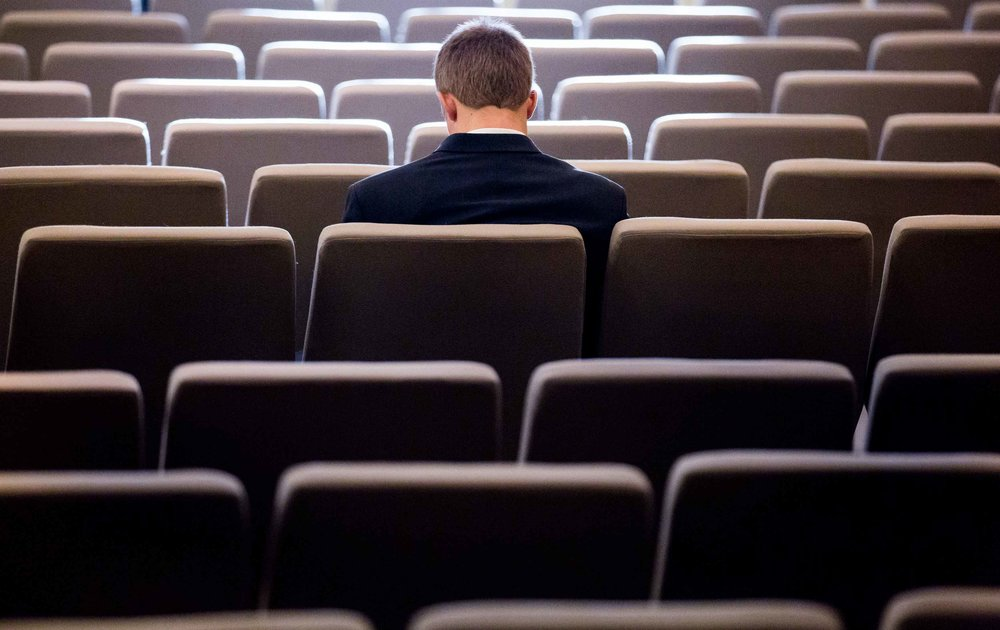 A man sits by himself after a conference ended in Indianapolis. Photo by Branden Camp