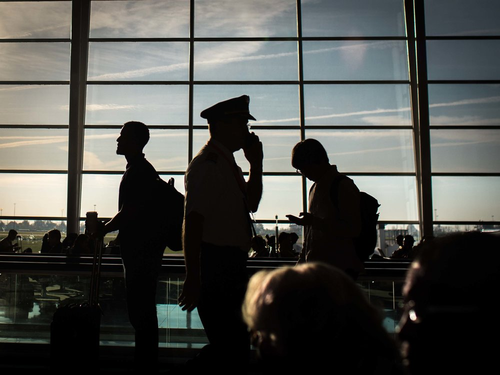Delta passengers wait to board a plane as an airline pilot walks through a terminal at Indianapolis International Airport in Indianapolis.  Photo by Branden Camp