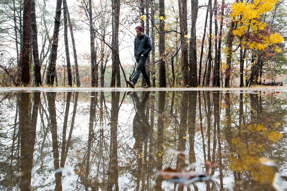A man is reflected in a puddle of water at the base of Kennesaw Mountain on an overcast day.  Branden Camp for AJC