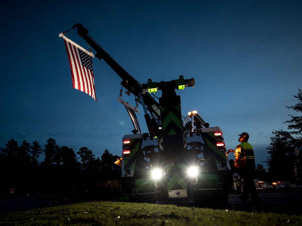 A statewide employee raises an American flag and a Thin Blue Line flag hang from one of their tow trucks, a company that regularly worked with Gwinnett police officer Antwan Toney, who was killed in the line of duty, Monday, Oct. 22, 2018, in Sugar Hill Ga. A Gwinnett County police officer on Monday shot and killed Maynard, 18, accused of fatally shooting police officer Antwan Toney on Saturday near a school in the Atlanta area, police said. (Branden Camp/Atlanta Journal-Constitution via AP)