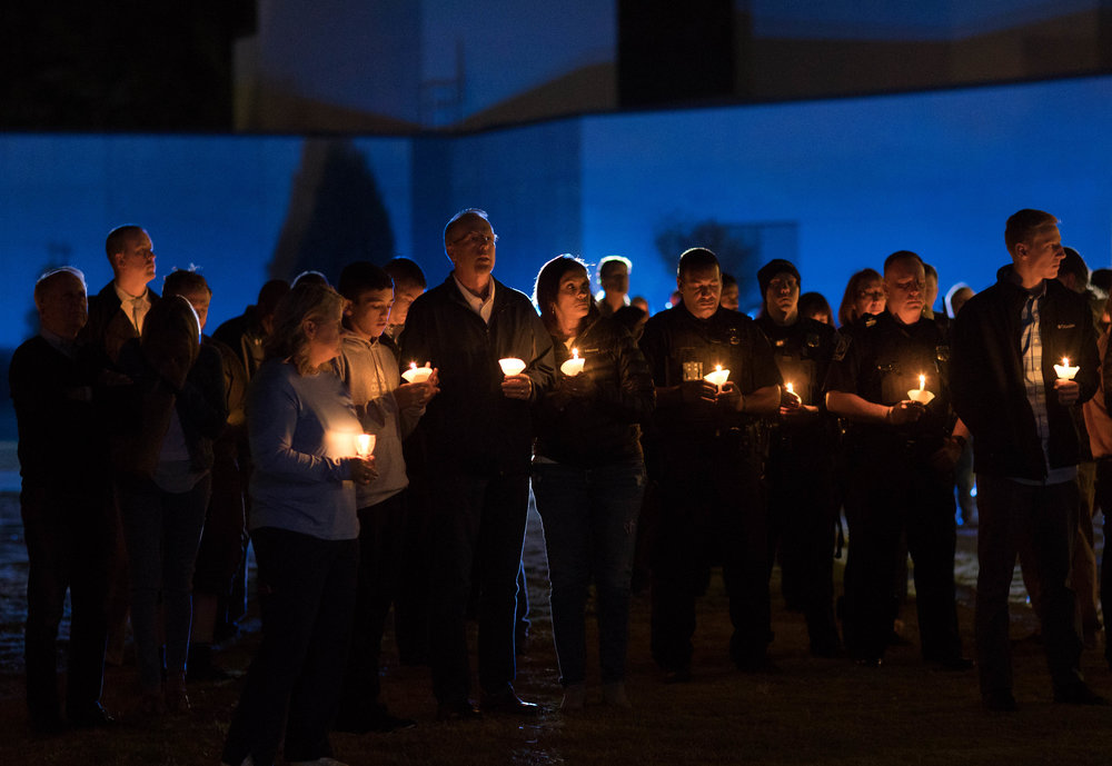 Police officers and members of the community hold candles during a candle light vigil for Gwinnett police officer Antwan Toney, who was killed in the line of duty, at Gwinnett Church, Monday, Oct. 22, 2018, in Sugar Hill, Ga. A Gwinnett County police officer on Monday shot and killed Maynard, 18, accused of fatally shooting police officer Antwan Toney on Saturday near a school in the Atlanta area, police said. (Branden Camp/Atlanta Journal-Constitution via AP)