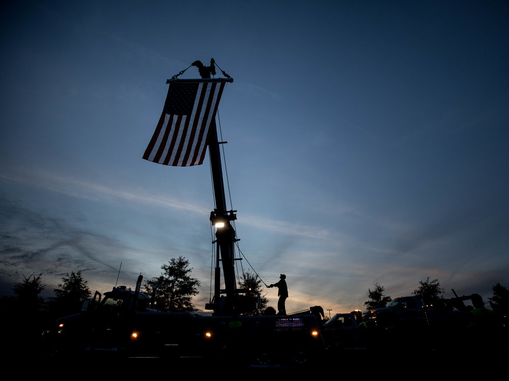 A Statewide employee raises an American flag from one of their tow trucks, a company that regularly worked with Gwinnett police officer Antwan Toney, who was killed in the line of duty, Monday, Oct. 22, 2018, in Sugar Hill Ga. A Gwinnett County police officer on Monday shot and killed Maynard, 18, accused of fatally shooting police officer Antwan Toney on Saturday near a school in the Atlanta area, police said. (Branden Camp/Atlanta Journal-Constitution via AP)
