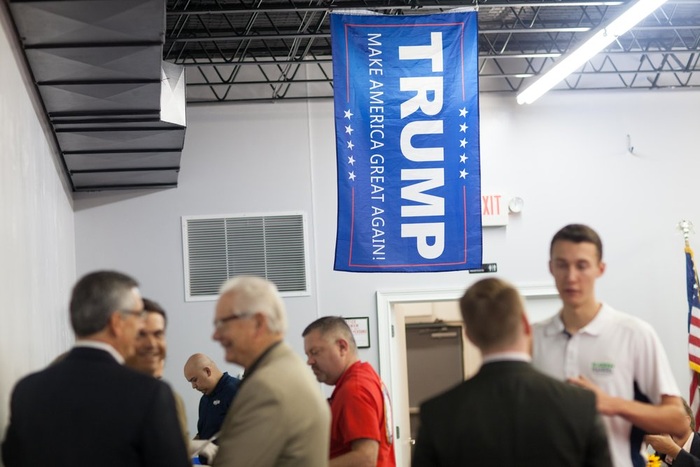 A Trump flag hangs from the ceiling as people talk during a breakfast meet and greet at the Cobb County GOP headquarters, Saturday, Oct.6, 2018, in Marietta, Ga.