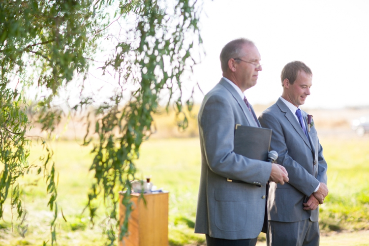 groom and officiant under willow tree during wedding ceremony