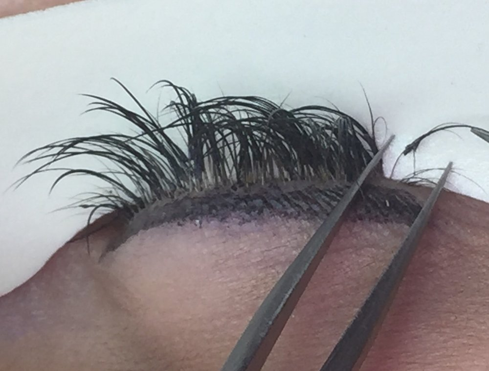 You can see how this extension is attached to multiple hairs and has excess adhesive. The extensions are also placed entirely too far from the base of the lash.