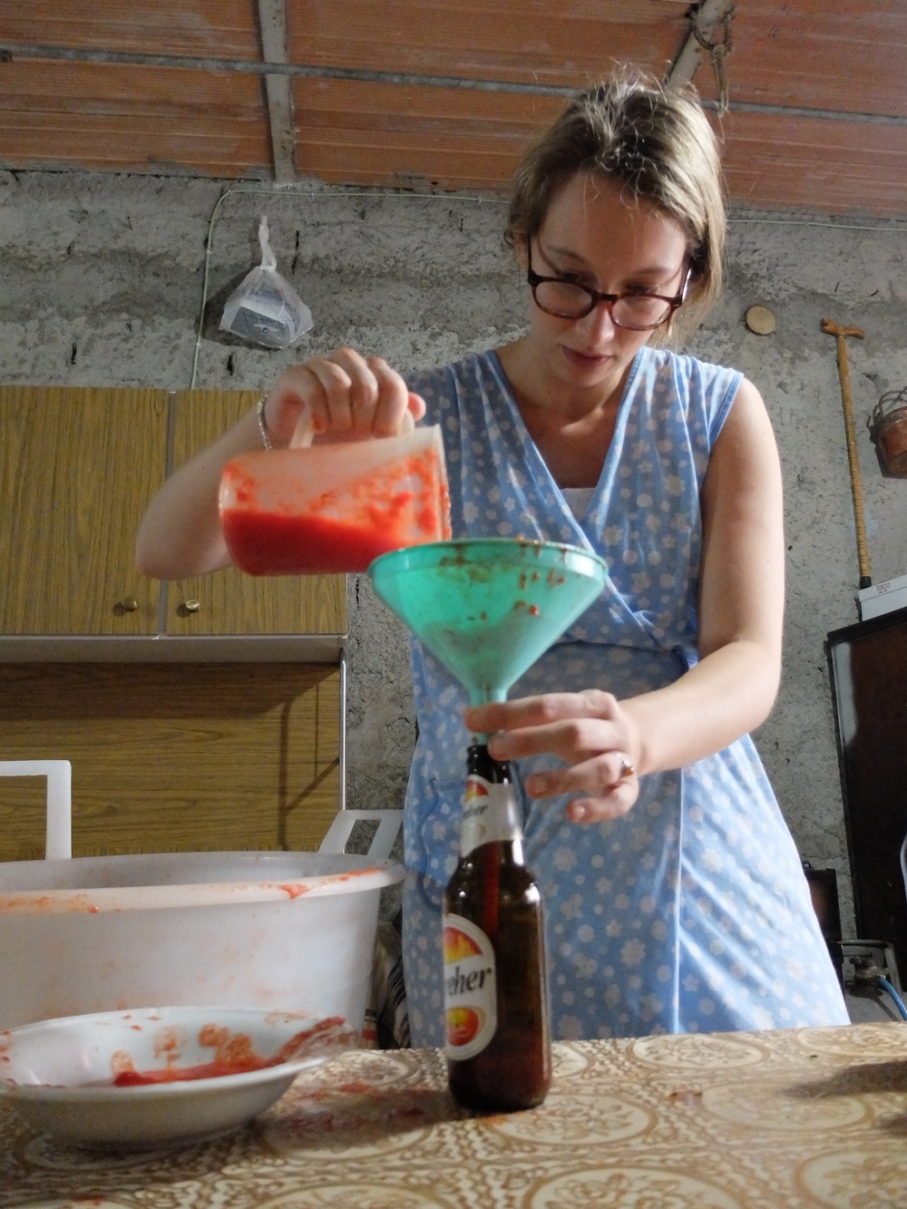 Simona filling up bottles with passata