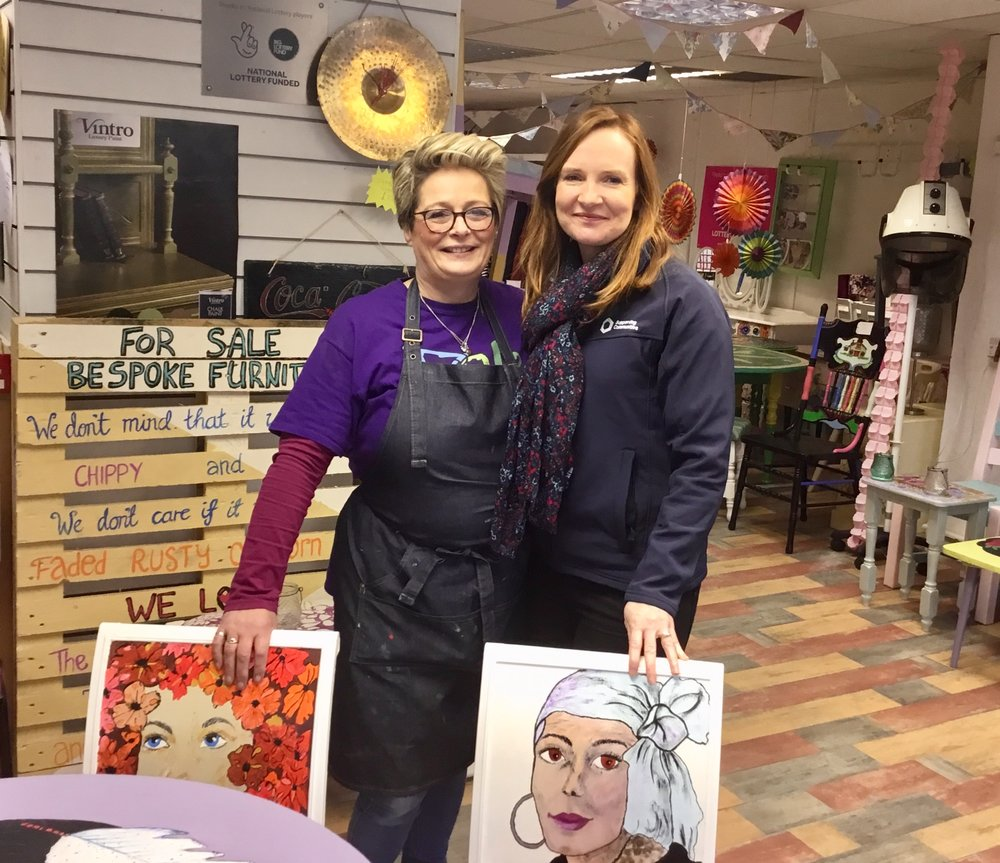 Ailish Teague, LCCL, and Orla McCann, Supporting Communities, pose with some hand painted furniture for sale in the LCCL shop.
