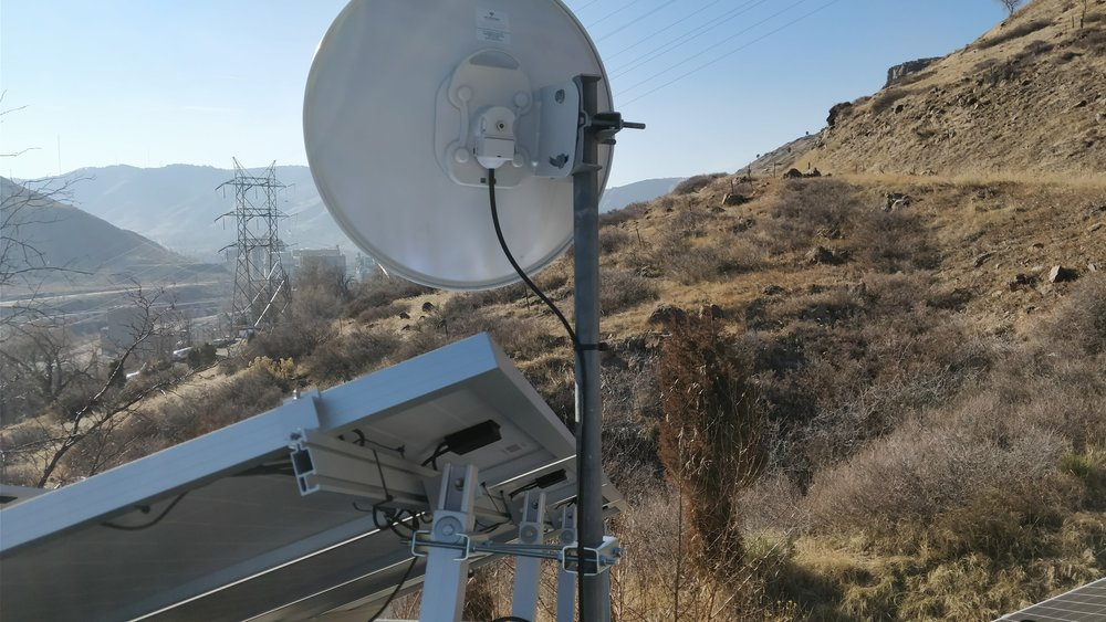 A dish antenna mounted to an existing solar panel support arm with a pipe