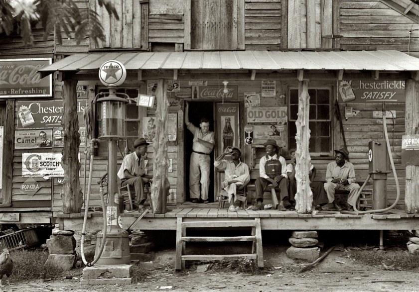 """Original caption: """"Country store on dirt road. Sunday afternoon. Note kerosene pump on the right and the gasoline pump on the left. Rough, unfinished timber posts have been used as supports for porch roof. Negro men sitting on the porch. Brother of store owner stands in doorway."""""""