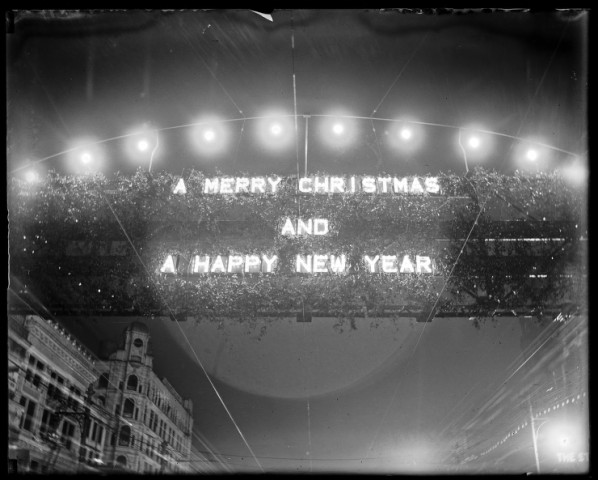 "One hundred years ago in New Orleans. ""A Merry Christmas and a Happy New Year"" message in lights strung over Canal Street near the intersection of Exchange Alley; Old Godchaux building visible at left. Date December 1916. Author: John Tibule Mendes. Wikimedia Commons."