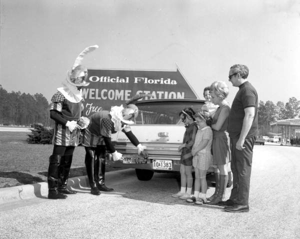 State Library and Archives of Florida, Local call number: C673303. Title: Costumed conquistadors applying bumper stickers near the Florida border. Date: ca. 1965. Photographer: Karl E. Holland, 1919-1993.