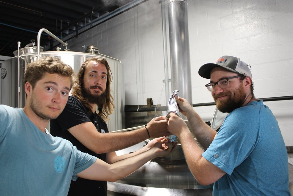 Dock Street Head Brewer Mark Russell (center) adds hops to the Down the Road batch of Down the Street with Antoine (left) and Isaiah (right) of Down the Road.