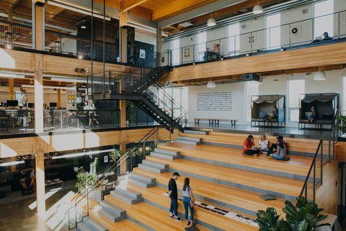 People working together inside the large atrium at Instrument's headquarters in Portland, OR.