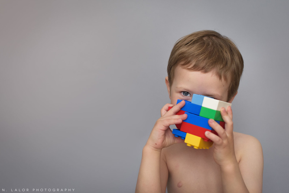 Simple portrait of a 4-year old boy with Lego Duplos, by N. Lalor Photography. Fairfield County, CT.