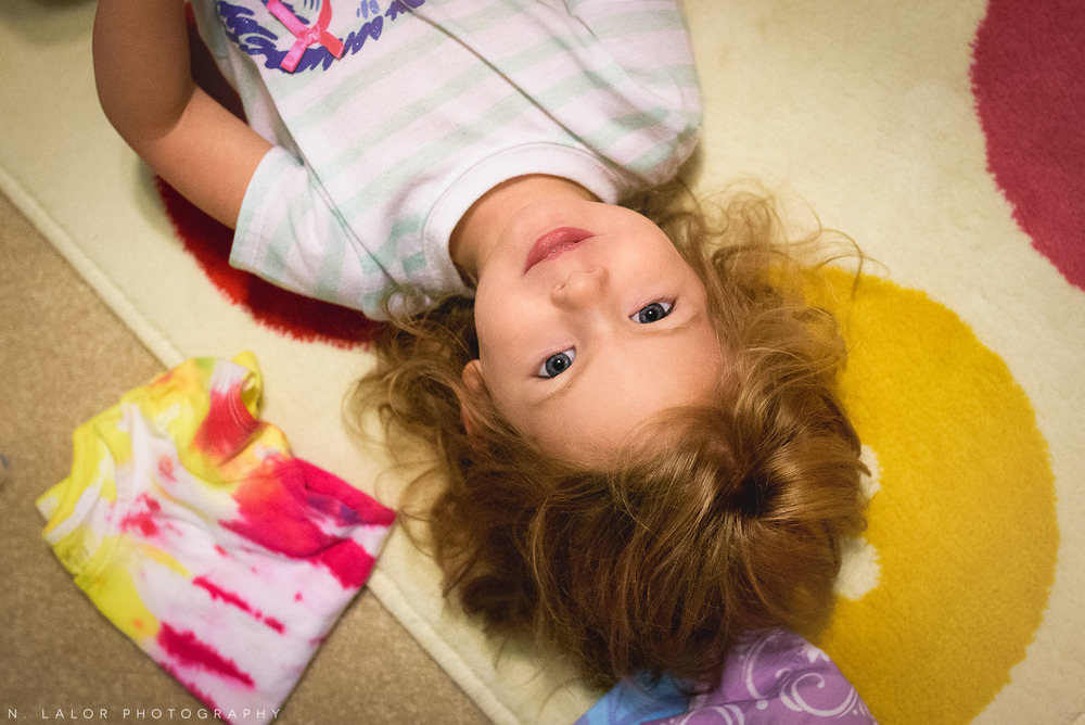 Getting a diaper change on the rug - portrait of a 2-year old girl. Documentary photo by N. Lalor Photography.