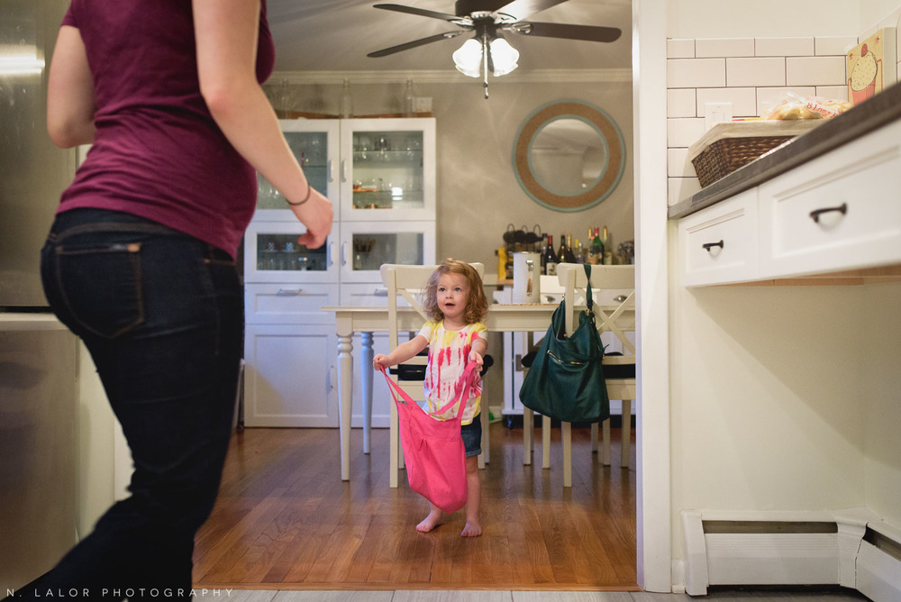 Getting ready for daycare, 2-year old girl asks Mom about her stuff. Documentary photo by N. Lalor Photography.