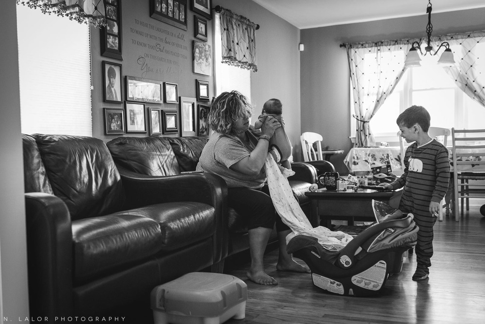 This is real life - Mom juggling two young boys early in the morning. Documentary photo by N. Lalor Photography.