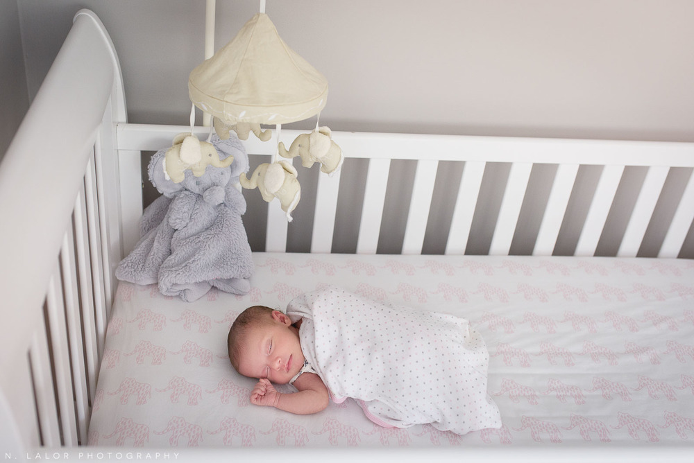 Baby girl peacefully sleeping in her crib. Lifestyle family with their newborn daughter in her elephant-themed nursery. Naturally styled photo by N. Lalor Photography.