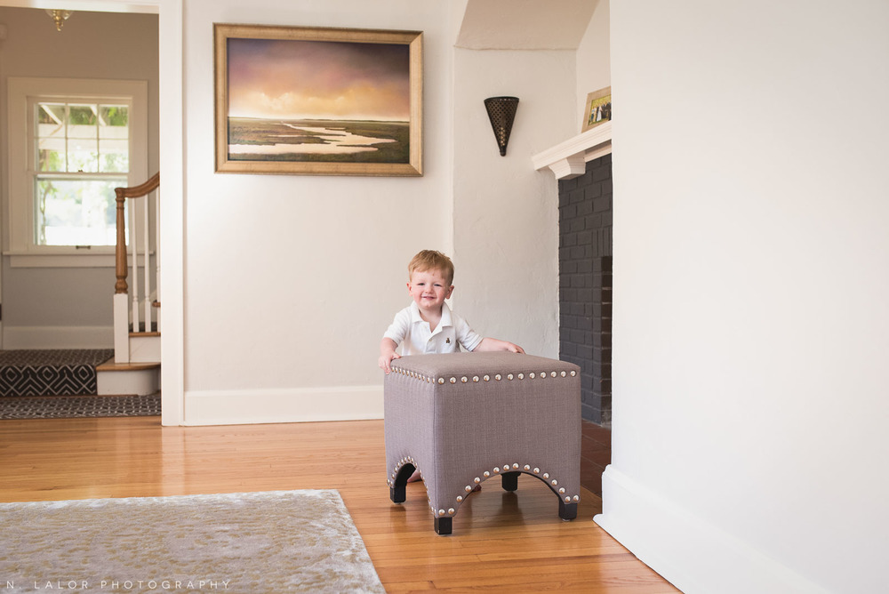 Pushing furniture around - a toddler has fun in the living room. Naturally styled family photo by N. Lalor Photography.